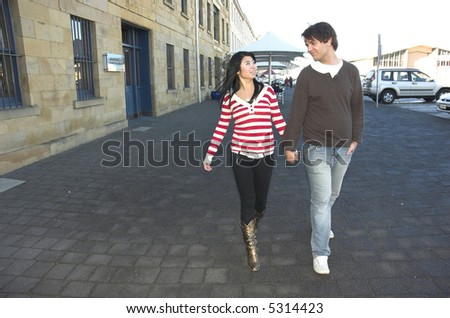 Cute young couple walking hand in hand.