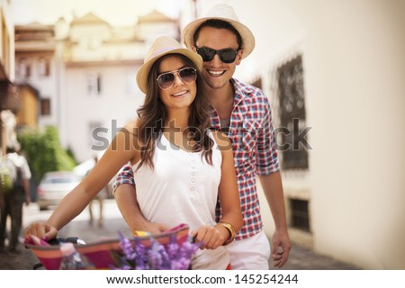 Cute young couple with bike - stock photo