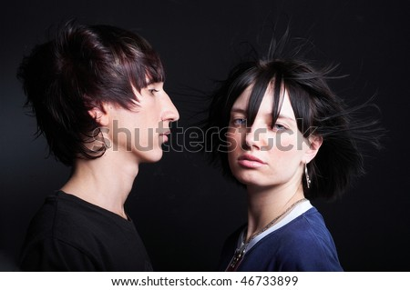 Cute young couple with fashion haircut, on black