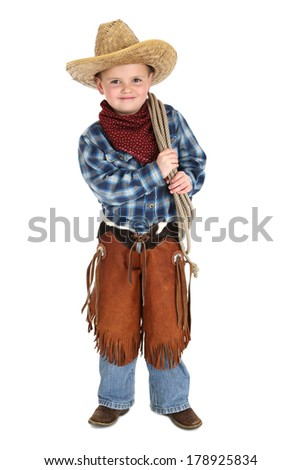 Cute young cowboy standing holding a rope