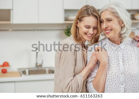 Cute young daughter embracing her mother with love