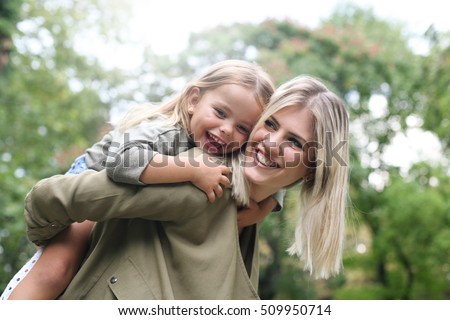 Cute young daughter on a piggy back ride with her mother.
