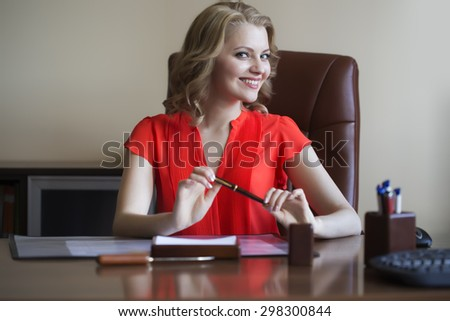 Cute young elegant smiling business woman sitting in office on brown leather chair in red blouse holding pen in hands looking forward indoor on white background, horizontal picture