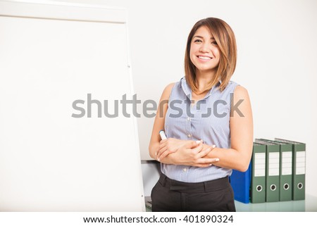 Cute young English professor standing next to a flip chart and smiling - stock photo