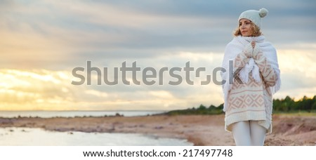 Cute young european woman in knitted clothes on the beach at sunset - stock photo
