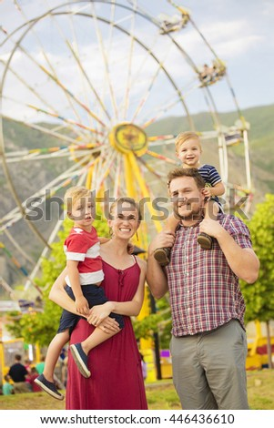 Cute young family enjoying a day at amusement park  - stock photo