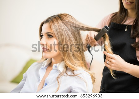Cute young female customer getting her hair straightened with a hair iron in a beauty salon