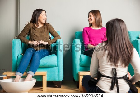 Cute young female friends relaxing and getting a foot massage at a beauty salon - stock photo