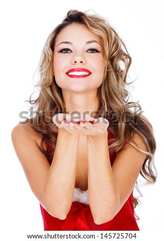 Cute young female in red dress blowing a kiss at you against white background  - stock photo