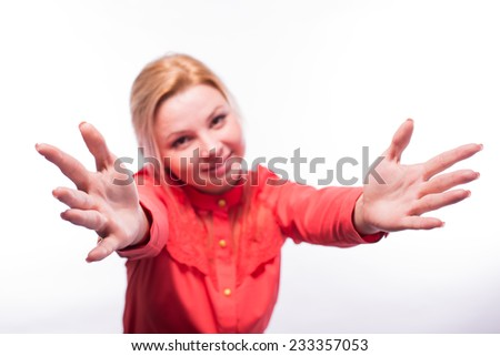 Cute young female in red dress blowing a kiss at you against white background
