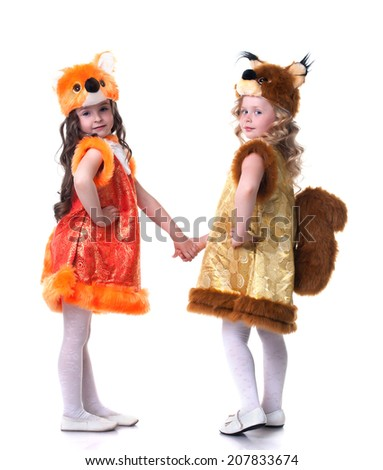 Cute young friends posing in carnival costumes - stock photo
