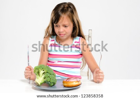 Cute young girl child making a choice between healthy broccoli vegetable and unhealthy sugary donut - stock photo