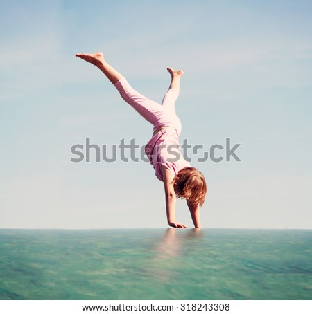 cute young girl doing handstand over blue sky - retro effect picture - stock photo