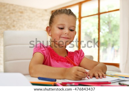 Cute young girl doing her math homework in school work book while sitting at living room table.