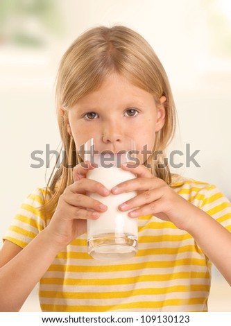 Cute young girl drinking a glass of milk