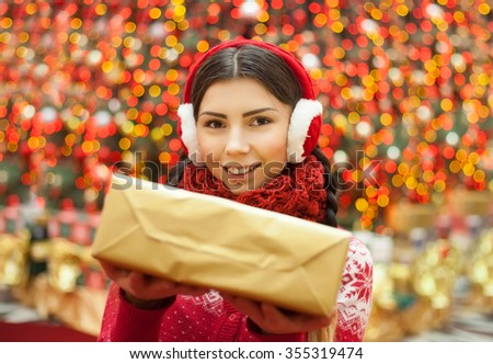 Cute young girl giving you present for Christmas and New Year in golden box