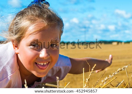 Cute young girl having fun on haystack. Stacks of straw - bales of hay, rolled into stacks left after harvesting of wheat ears, agricultural farm field with gathered crops rural. Pargi, Voka, Estonia