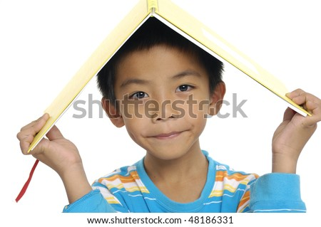Cute young girl holding book on head - stock photo