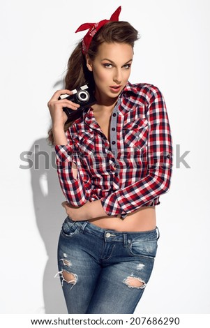 cute young girl holding retro camera in fashion pose at the studio  - stock photo