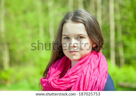 Cute young girl in a forest wearing a pink scarf