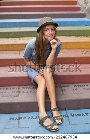 Cute young girl in a hat sitting on the stairs outdoors. - stock photo