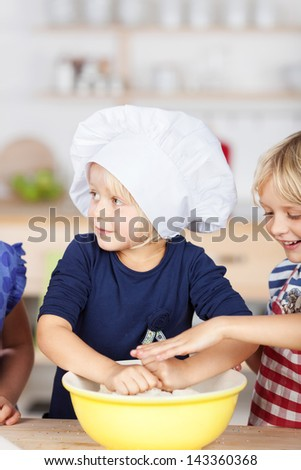 Cute young girl in a large chefs hat kneading dough in a bowl watched by her mischievous little sister - stock photo