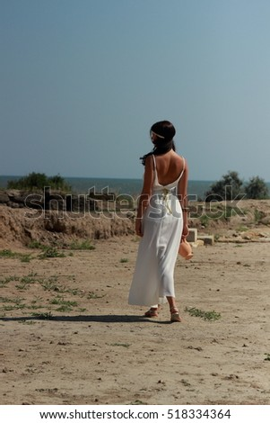 Cute young girl in a long white dress in Greek style goes on the excavations of the ancient city of Nymphaeum, Kerch, Russia