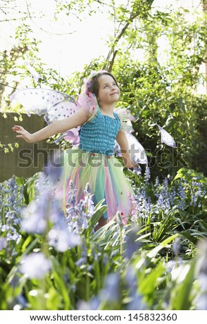 Cute young girl in fairy costume standing at flower garden - stock photo
