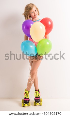Cute young girl in roller skates holding colorful balloons against white background.