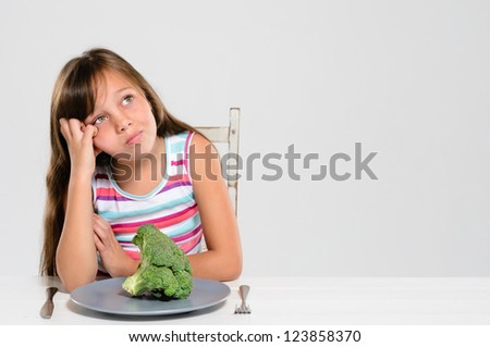 Cute young girl is bored with her food, looking up and uninterested in vegetables and healthy produce - stock photo
