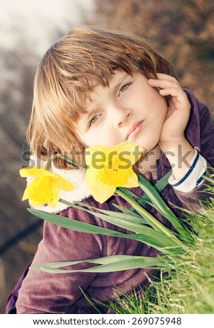 cute young girl lying on the grass with narcissus - vintage image look - stock photo
