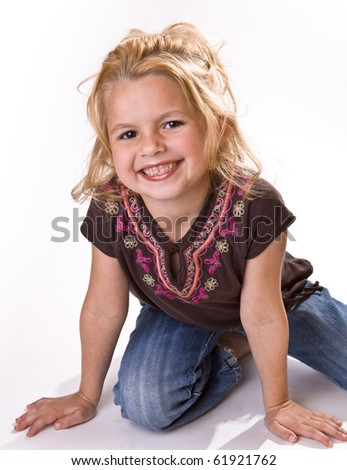 Cute young girl, on her knees smiling for the viewer