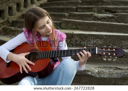 Cute Young Girl Playing a Guitar Against Old Stone Staircase - stock photo