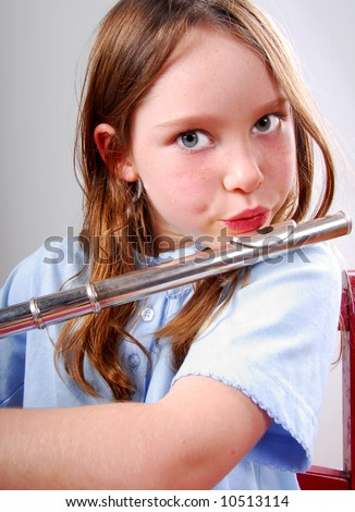 Cute young girl playing flute on chair - stock photo