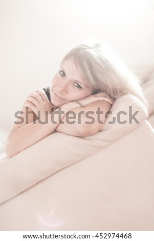 Cute young girl relaxing on couch at home. Hi key Softfocus Image - stock photo