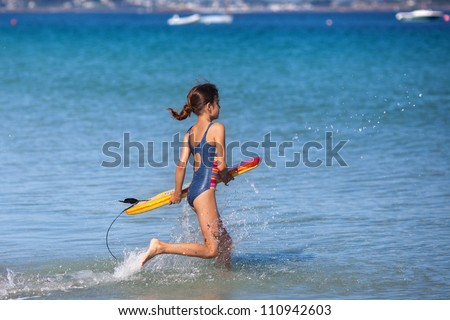 cute young girl runs with her surfboard in the sea water