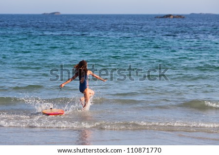 cute young girl runs with the surfboard in the sea - stock photo