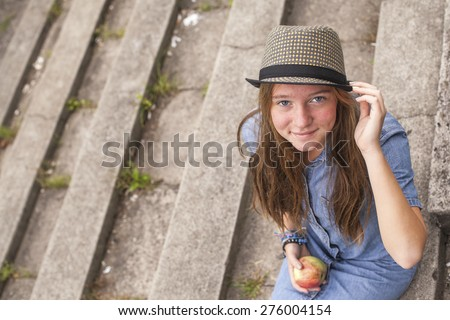 Cute young girl sitting on the stone steps, top view, looking at the camera. - stock photo