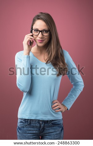 Cute young girl smiling on the phone with glasses - stock photo