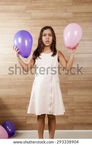 Cute young girl smilling, playing with balls. - stock photo