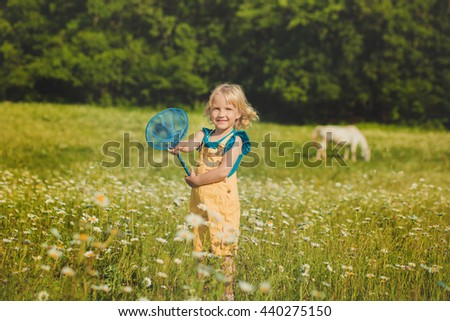 Cute young girl standing on a lavender field in blue jeans jacket with purple Teddy bear in her hands.