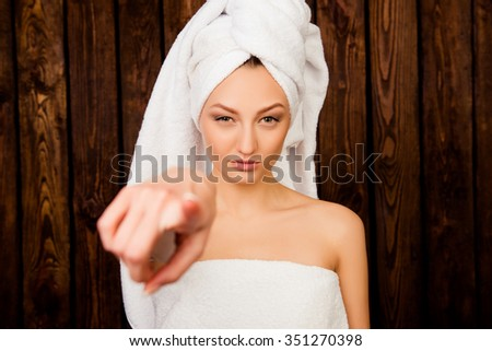 Cute young girl stares and point with her finger - stock photo