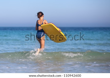 cute young girl walks with her surfboard in the sea
