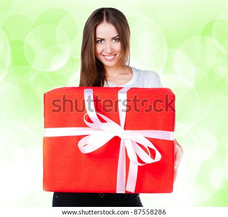 cute young girl with a gift on a green blur background - stock photo
