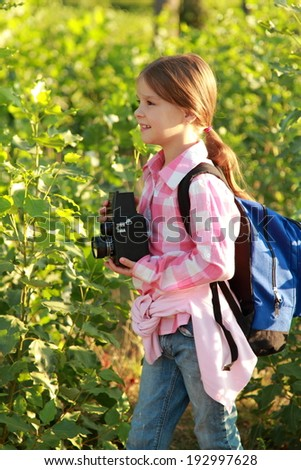 Cute young girl with a school backpack and a camera takes pictures of plants for a school lesson in the forest - stock photo