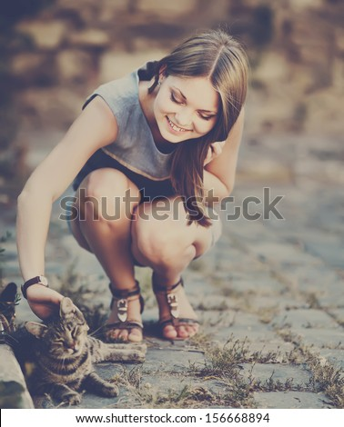 cute young girl with a smile playing with cat at street. - stock photo