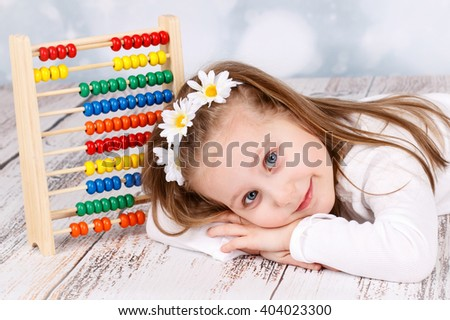 Cute young girl with abacus - stock photo