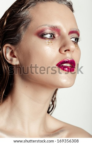 Cute young girl with creative make-up art. Glitter on her face, monochrome eyelashes, wet hair and fuchsia lips