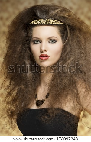 cute young girl with long curly hair-style and leopard accessory posing with pretty make-up and looking in camera  - stock photo