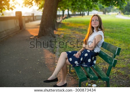 Cute young girl with long golden hair sitting alone on a bench in the Park.  - stock photo